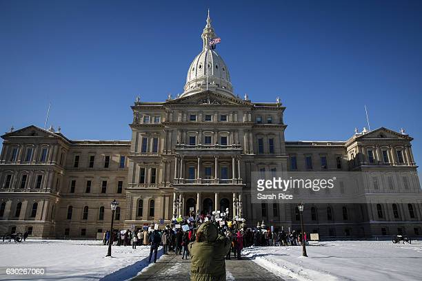 Protestors rally at the Michigan State Capitol before the state electoral college met to cast their votes on December 19 2016 in Lansing Michigan...