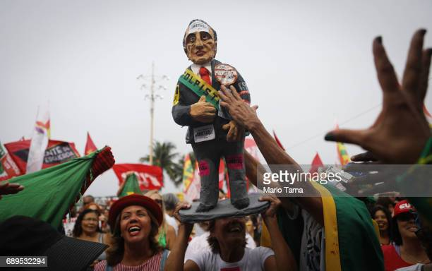 Protestors rally holding a doll representing President Michel Temer at a demonstration and concert calling for direct presidential elections on May...