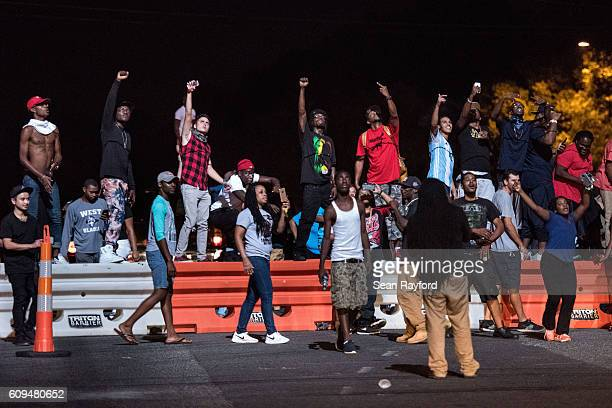 Protestors react to a police helicopter during protests in the early hours of September 21 2016 in Charlotte North Carolina The protests began last...