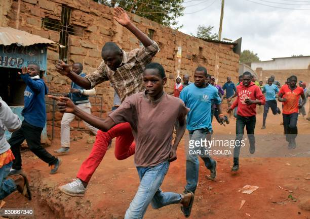 Protestors run away after riot police fired live rounds in the Kibera slum in Nairobi on August 12 2017 Three people including a child have been shot...