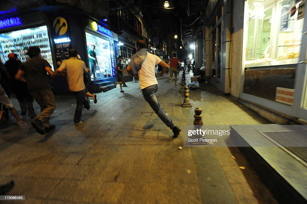Protestors run from a volley of gas as Turkish police use tear gas and water cannons to battle anti-government protestors along the Istikhlal shopping avenue near Taksim Square on July 6, 2013 in the heart of Istanbul, Turkey. The protests began in late May over the Gezi Park redevelopment project and saving the park trees adjacent to Taksim Square but swiftly turned into a protest aimed at Prime Minister Recep Tayyip Erdogan and what protestors call his increasingly authoritarian rule. The protest spread to dozens of cities in Turkey, in secular anger against Erdogan and his Islam-rooted Justice and Development Party (AKP).