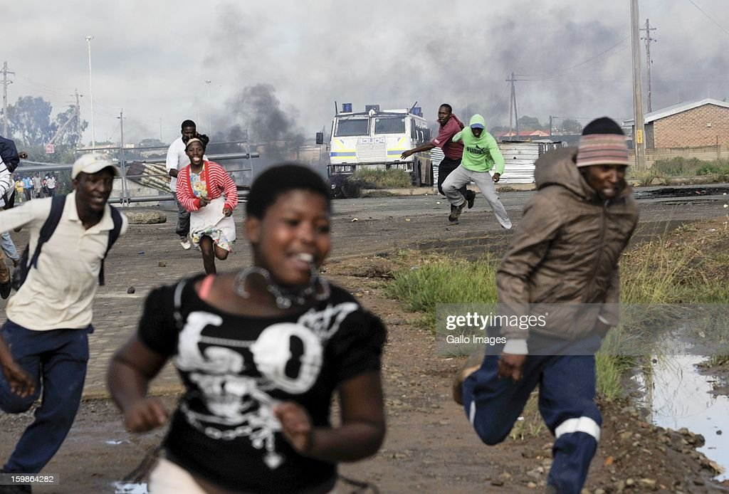 Protestors run from the police on January 21, 2013, in Sasolburg, South Africa. Protesting broke out as a result of the announcement of the intention to integrate municipal systems from Sasol to Parys.
