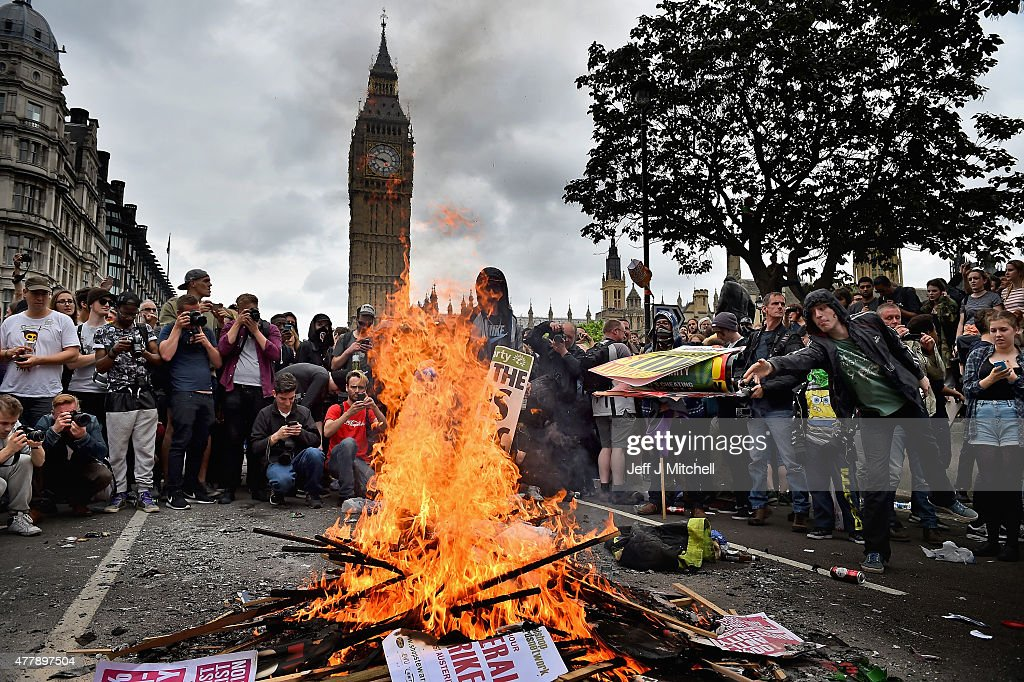 Protestors set fire to placards in central London during demonstrating against austerity and spending cuts on June 20 2015 in London England...