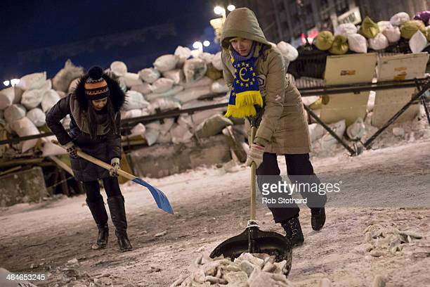 Protestors shovel snow to reinforce barricades on streets leading to Independence Square on January 23 2014 in Kiev Ukraine Talks to resolve the...
