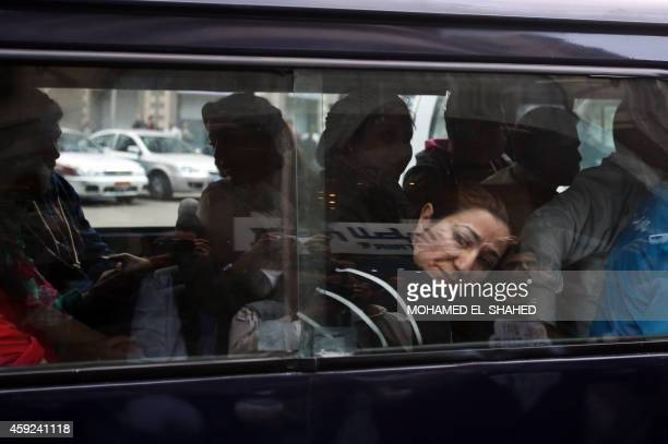 Protestors sit in a police vehicle after being detained during an antimilitary demonstration marking the third anniversary of the 2011 protests...