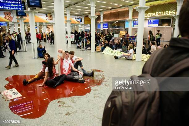 Protestors sit in fake blood next to the entrance of the Eurostar train at the Saint Pancras rail station in London on October 16 during a...