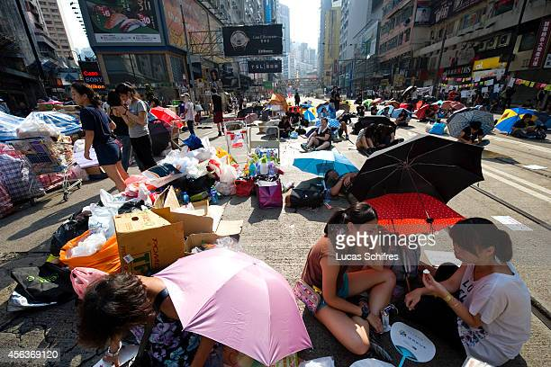 Protestors sit under umbrellas to protect themselves from the sun as part of a prodemocracy sitin known as 'Occupy Central' blocking traffic on...