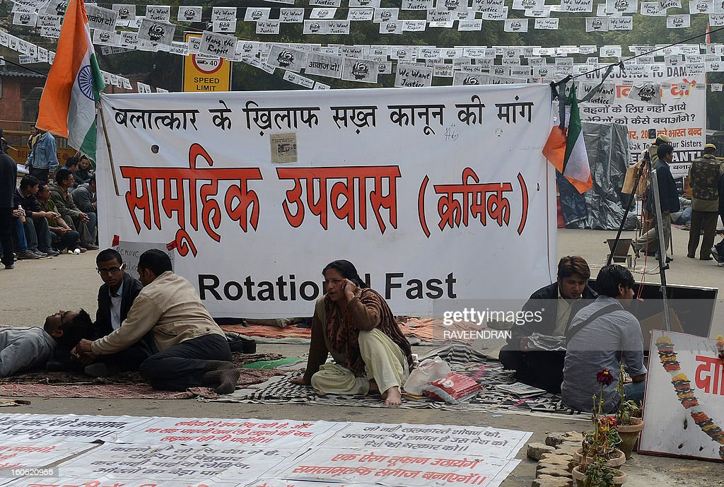 Protestors sits in front of a banner during a protest against last month's gang rape and murder of a student, in New Delhi on February 2, 2013. India's cabinet has approved harsher punishments for rapists, including the death penalty, after a brutal gang-rape in New Delhi that sparked national outrage.
