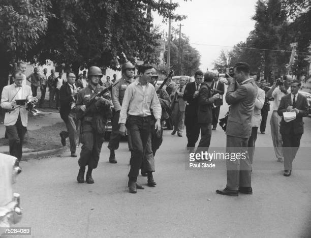 Protestors soldiers and journalists gathered in the street in Little Rock Arkansas where the first school desegregation in the US at Central High...