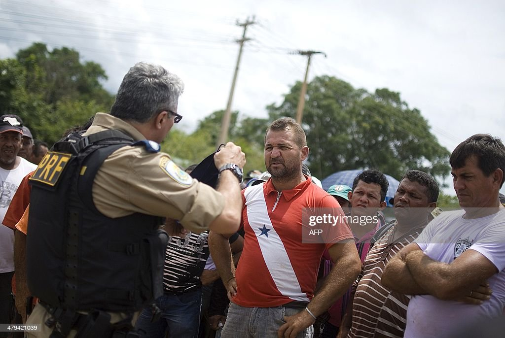 Protestors speak with a police officer during a demonstration against Norte Energia - the company responsible for the construction of Belo Monte hydroelectric power plant - demanding compensation for the loss of income from the flooding of the Xingu river near Altamira, in the northern state of Para, Brazil, on March 18, 2014. The dam will be the largest hydroelectric power plant in Brazil and provide 11% of the nation's electricity. Norte Energia says about 502km2 will be flooded and 117 social, economic and environmental projects are underway for the millions affected in the region.
