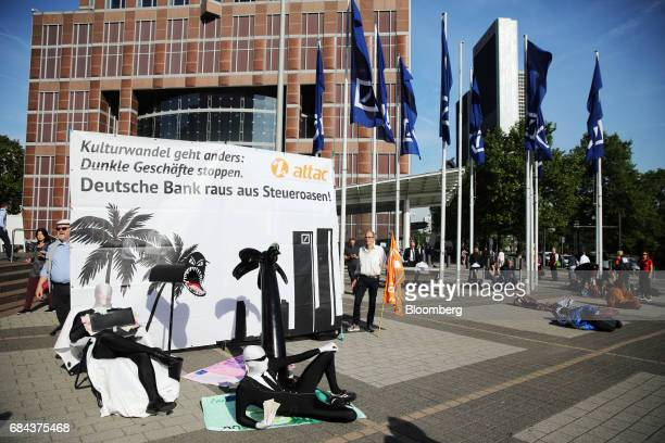 Protestors stage a 'taxoasis' demonstration outside the Deutsche Bank AG headquarters office ahead of the bank's annual general meeting in Frankfurt...