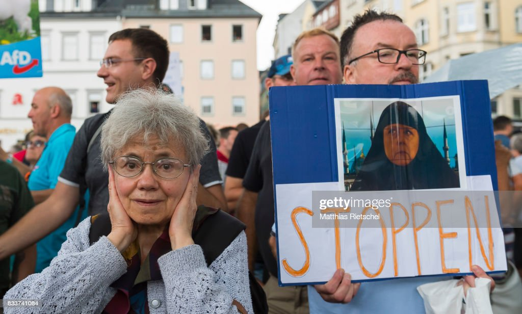 Protestors stand close to a place, where German Chancellor and head of the German Christian Democrats (CDU) Angela Merkel delievers a speech during an election rally in the state of Saxony on August 17, 2017 in Annaberg-Buchholtz, Germany. Germany is scheduled to hold federal elections on September 24 and Merkel, who is running for a fourth term as chancellor, currently holds a double-digit lead over Martin Schulz from the German Social Democrats (SPD), her main opponent.