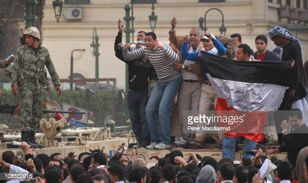 Protestors stand on army tanks in Tahrir Square on January 29 2011 in Cairo Egypt Tens of thousands of demonstrators have taken to the streets across...