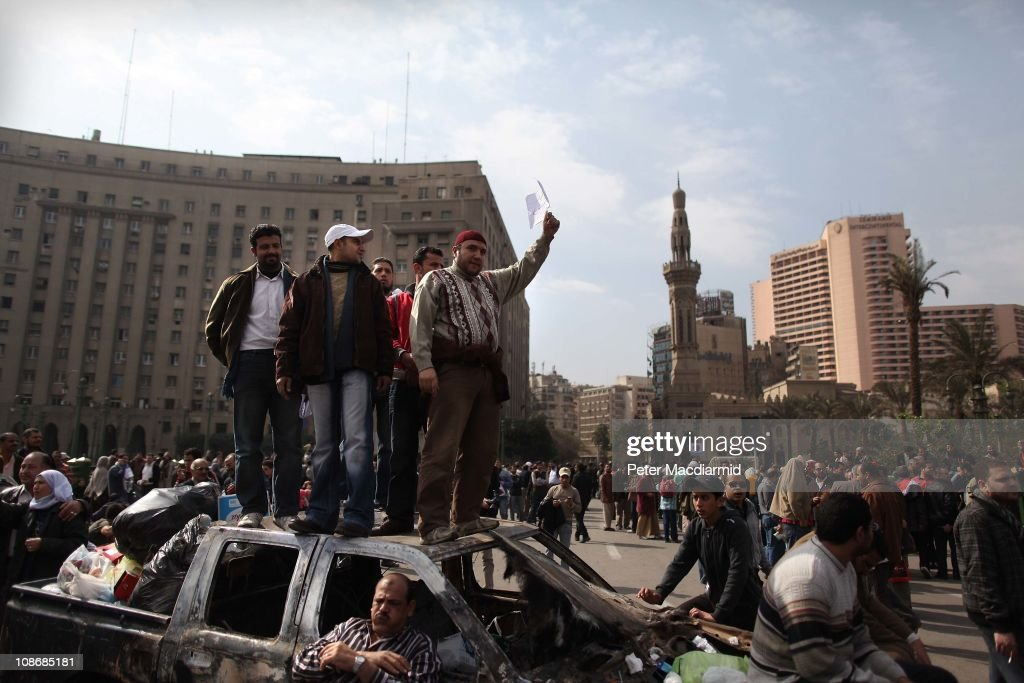 Protestors stand on the remains of a burn out car in Tahrir Square on February 1, 2011 in Cairo, Egypt. The Egyptian army has said it will not fire on protestors as they gather in large numbers in central Cairo demanding the resignation of Egyptian President Hosni Mubare.