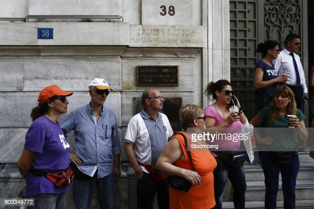 Protestors stand outside a National Bank of Greece SA bank branch during a demonstration by municipal contract workers in Athens Greece on Thursday...