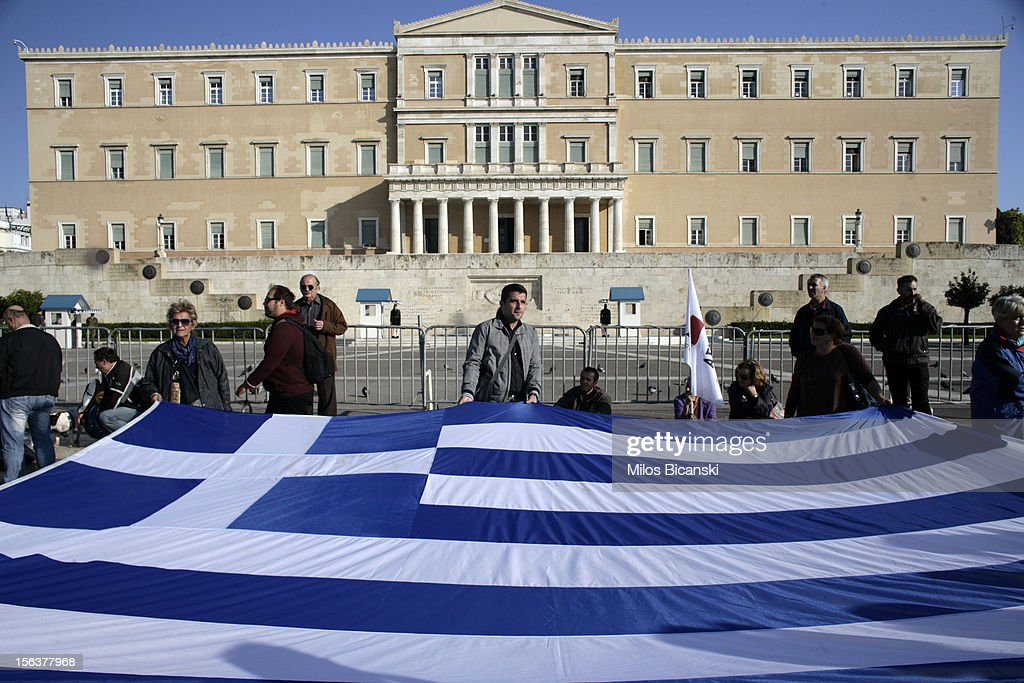 Protestors stand with a Greek flag outside the Greek parliament during an anti-austerity protest on November 14, 2012 in Athens, Greece. Unions in Spain, Portugal and Greece went on strike in what has become the first broad-based anti-austerity action to protest government plans amid a wide economic scope across Europe.