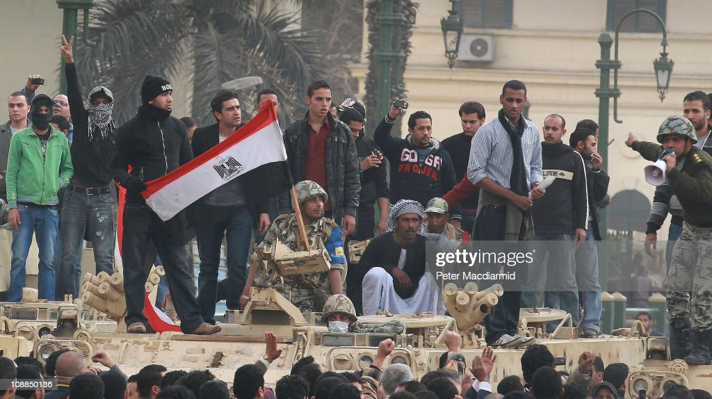 Protestors stand with a soldier as he waves an Egyptian flag on an army tank in Tahrir Square on January 29 2011 in Cairo Egypt Tens of thousands of...