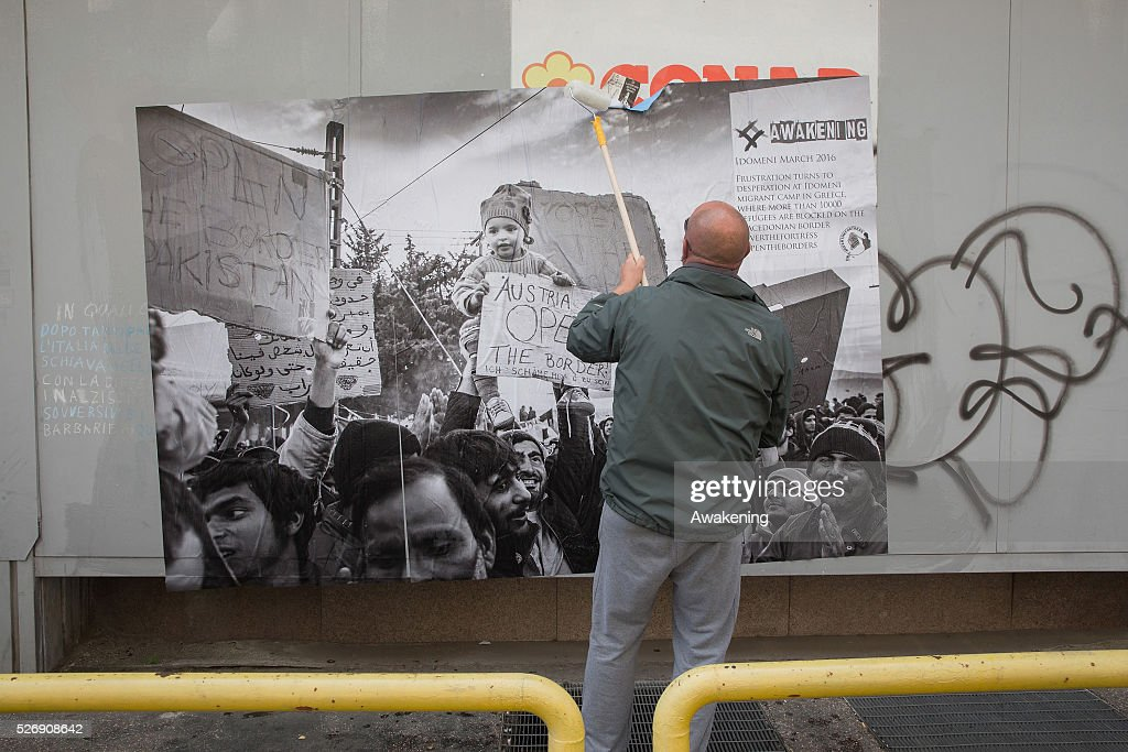 Protestors stick a poster during May Day protests on May 01, 2016 in Rome, Italy. Police clashed with protestors as hundreds took to the streets to participate in May Day marches and gatherings across Italy, with many demonstrators demanding a solution to the migrant crisis.