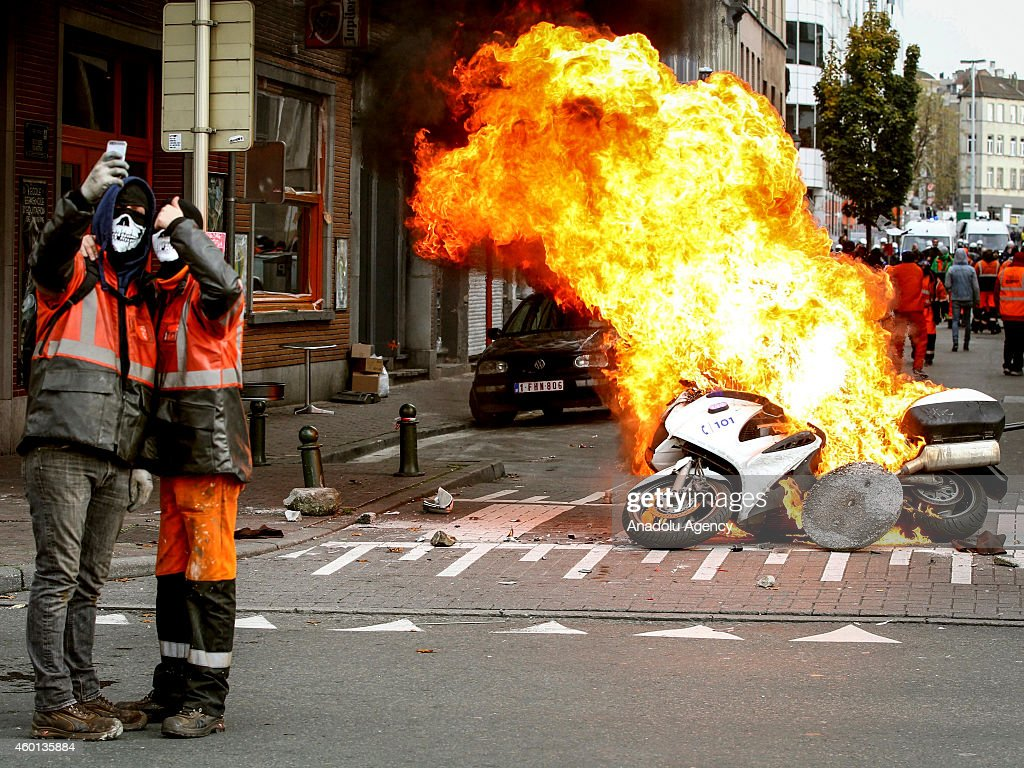 Protestors take a selfie in front of burning police motorbike in Brussels, on November 6, 2014. Belgians protest government's policies that will extend the pension age, contain wages and cut into public services.