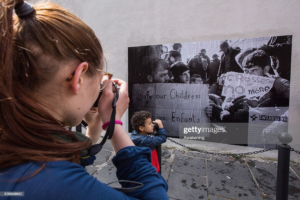 Protestors take pictures of a poster during May Day protests on May 01, 2016 in Rome, Italy. Police clashed with protestors as hundreds took to the streets to participate in May Day marches and gatherings across Italy, with many demonstrators demanding a solution to the migrant crisis.