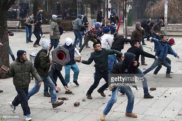 Protestors throw bricks and stones as they clash with riot police during a demonstration in Pristina on January 27 2015 Several people were injured...