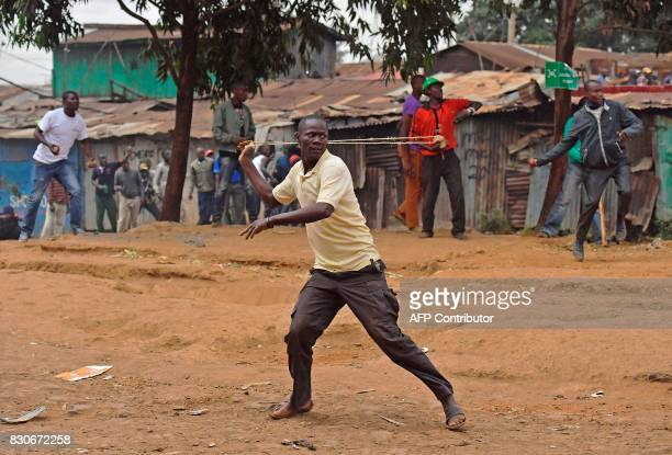 Protestors throw stones during clashes with riot police in the Kibera slum in Nairobi on August 12 2017 Three people including a child have been shot...