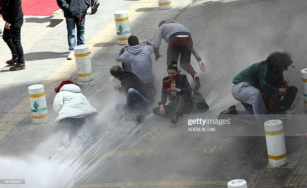 Protestors try to take shelter as riot police uses water cannons during clashes after hundreds of people tried to reach the city's main Kizilay...