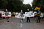 Protestors walk across the road with placards outside the gates to the Cuadrilla site on July 31 2013 in Crawley West Sussex Protesters continue to...