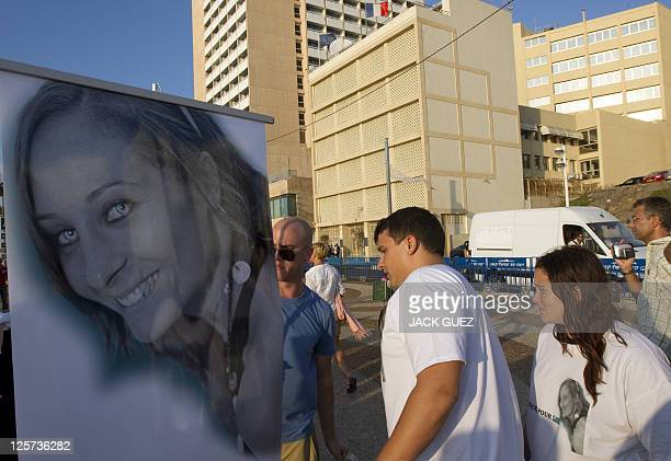 Protestors walk past a photo of Lee Zeituni a 25yearold gym instructor killed last week in a hit and run incident as they demonstrate outside the...