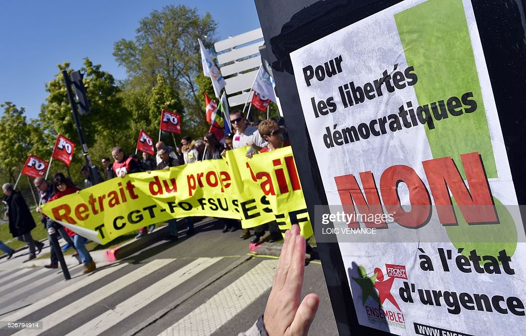 Protestors walk past a sign reading 'For democratic freedom, No to the state of emergency' during the traditional May Day rally in Nantes, western France, on May 1, 2016. / AFP / LOIC