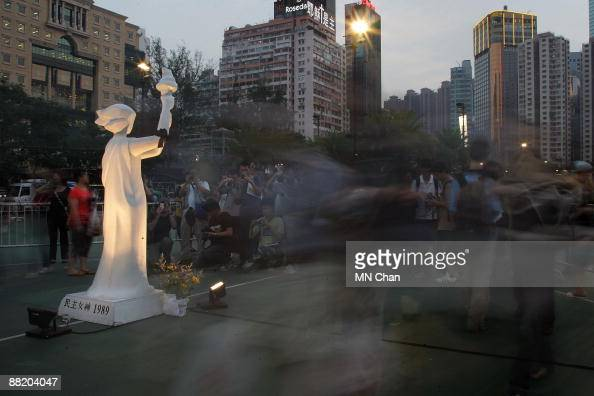 Protestors walk past the statue of the Goddess of Democracy during a candlelight vigil for the 20th anniversary of June 4 Tiananmen Square Massacre...