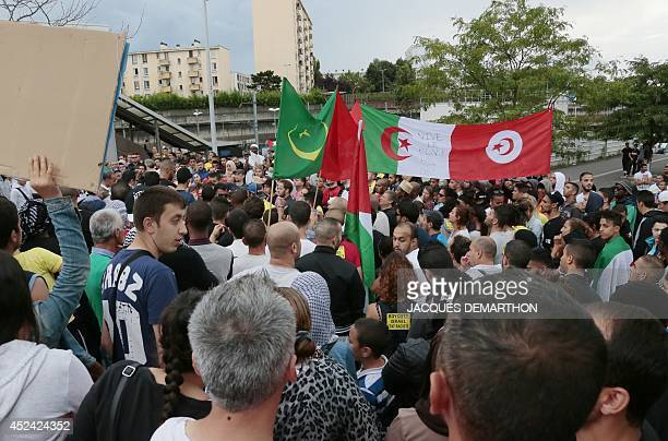 Protestors wave Mauritanian Algerian and Tunisian national flags as they gather near a railway station in Sarcelles a suburb of Paris on July 20 to...