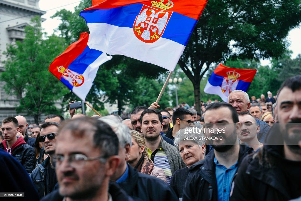 Protestors wave Serbian flags in front of the Electoral Commission in downtown Belgrade on April 30, 2016 during a protest organised by Serbian main opposition parties against alleged electoral 'fraud' at last weekend polls. The protest held in front of the Electoral Commission in downtown Belgrade came after the latest results showed a far-right coalition has been excluded from parliament after narrowly missing the five percent threshold needed for seats in final results. / AFP / ALEXA