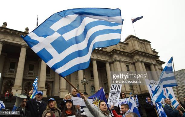Protestors wave the Greek flag as they shout 'Oxi' during the Melbourne stands with Greece solidarity rally outside Parliament House in Melbourne on...
