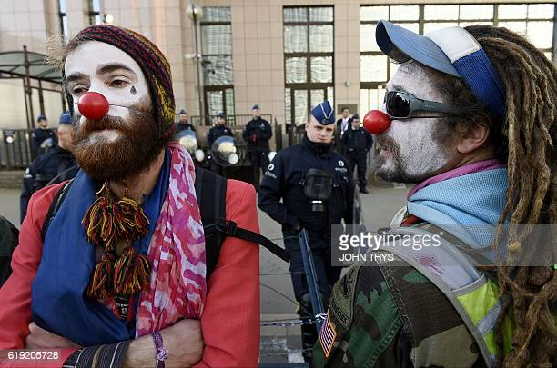 Protestors wearing clown make up stand before a police barricade before the start of the EUCanada summit to conclude the Comprehensive Economic and...