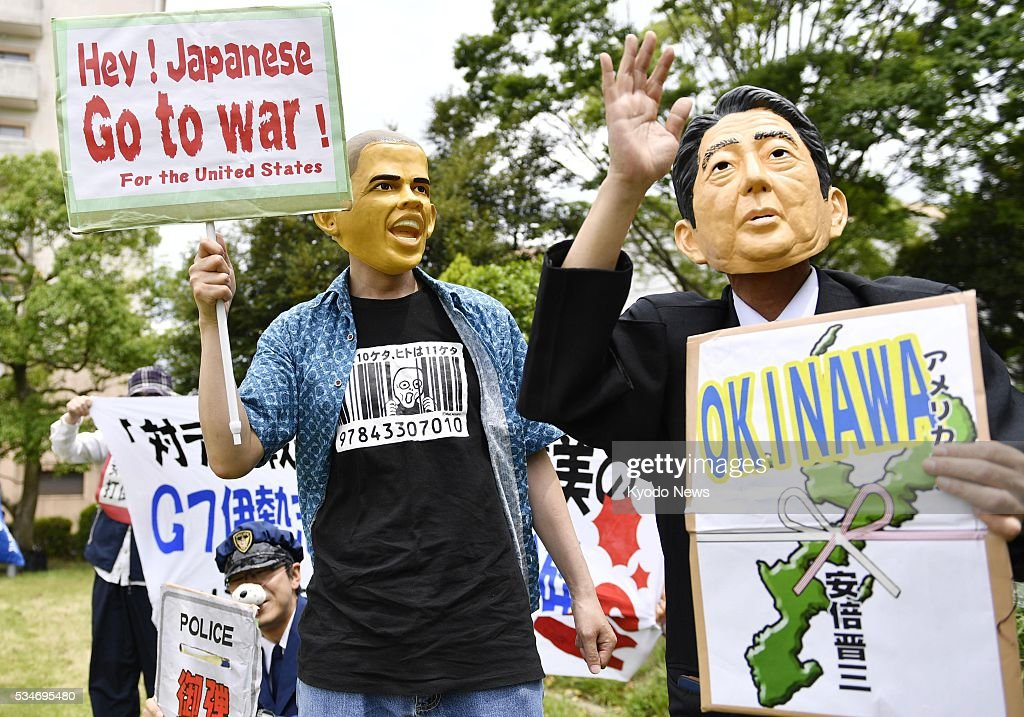 Protestors wearing face masks of U.S. President Barack Obama and Japanese Prime Minister Shinzo Abe display messages objecting to their security policies in Shima, Mie Prefecture on May 27, 2016, where Abe is hosting a summit of the Group of Seven major economies.