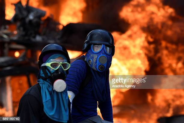 Protestors wearing gas masks stand in front a burning truck during a protest against the government of Venezuelan President Nicolas Maduro in Caracas...
