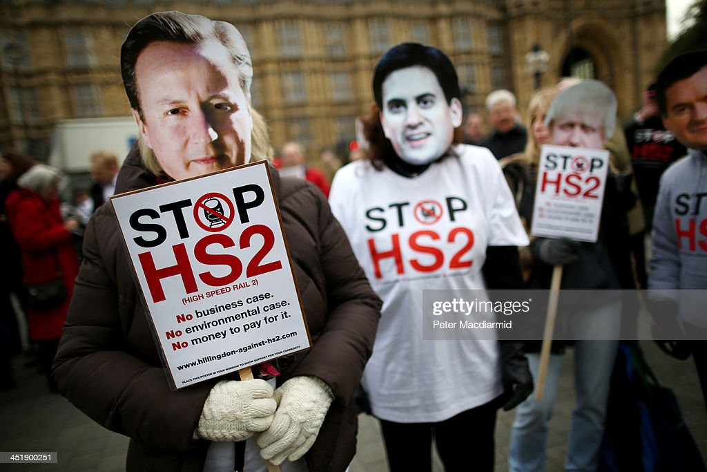 Protestors wearing masks depicting Prime Minister David Cameron (L), Labour Party Leader Ed Miliband and London Mayor Boris Johnson (R) demonstrate against the High Speed 2 (HS2) rail line at Parliament on November 25, 2013 in London, England. Legislation for the proposed HS2 line between London and Birmingham will be presented to Parliament today, in an attempt to gain support from MPs.