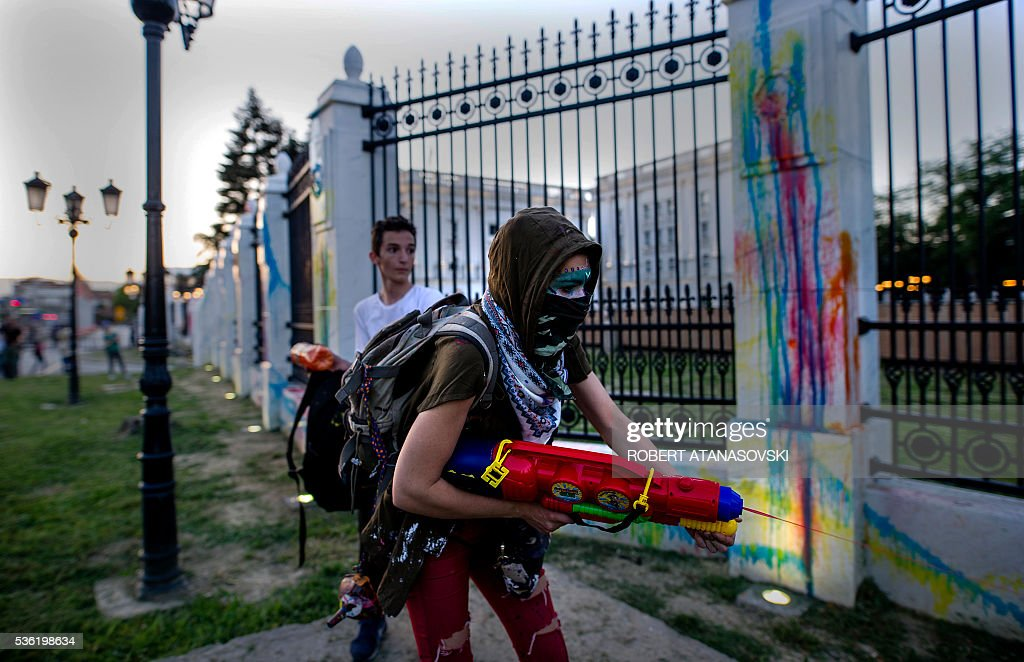 Protestors wearing masks use water guns to spray colored paint on the Government building fence during an anti-government protest in Skopje on May 31, 2016, in a series of protests dubbed Colourful Revolution. Macedonia's president revoked on May 27 the pardons he had granted to 22 politicians implicated in a wiretapping scandal, after the move sparked outrage inside and outside the troubled Balkan country. / AFP / Robert ATANASOVSKI