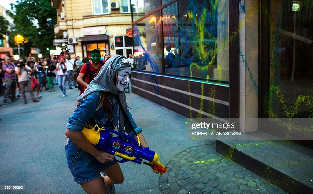 Protestors wearing masks use water guns to spray coloured paint on the public office of President Gjorge Ivanov during an anti-government protest in Skopje on May 31, 2016, in a series of protests dubbed Colourful Revolution. Macedonia's president revoked on May 27 the pardons he had granted to 22 politicians implicated in a wiretapping scandal, after the move sparked outrage inside and outside the troubled Balkan country. / AFP / Robert ATANASOVSKI