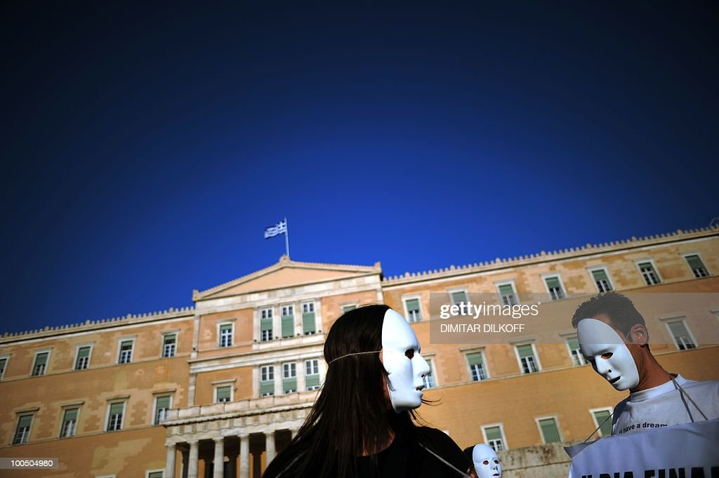 Protestors, wearing white masks, stand outside the Greek Parliament in the center of Athens on May 9, 2010. Greece's finance minister said on May 9 an unpopular EU-IMF austerity deal could be modified if cutbacks work, as a new poll showed Greeks accepting the belt-tightening to prevent default.