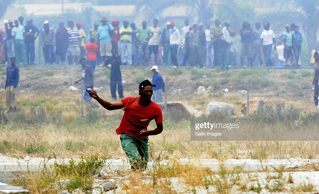 Protestrs stone cars at the N1 highway De Doorns on January 9, 2013, in Cape Town, South Africa. The farm workers went on strike, demanding wages of R150 a day.