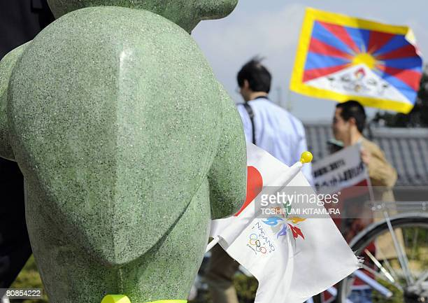 ProTibet demonstrators march past a statue holding 1998 Nagano Olympic flag in central Nagano city on April 25 2008 a day before the Beijing Olympic...