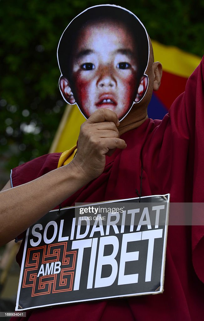 A pro-Tibetan protester holds a picure of Gendun Cheokyi Nyima (The Panchen Lama) during a demonstration outside the Chinese consulate in Barcelona on May 17, 2013 in Barcelona, to demand human rights freedom in Tibet and dialogue between the Dalai Lama and Beijing.