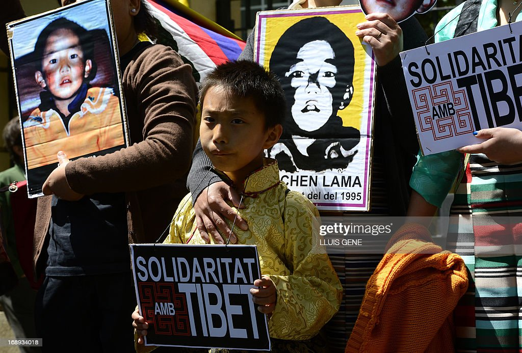 Pro-Tibetan protestors hold picures of Gendun Cheokyi Nyima (The Panchen Lama) during a demonstration outside the Chinese consulate in Barcelona on May 17, 2013 in Barcelona, to demand human rights freedom in Tibet and dialogue between the Dalai Lama and Beijing. AFP PHOTO/LLUIS GENE