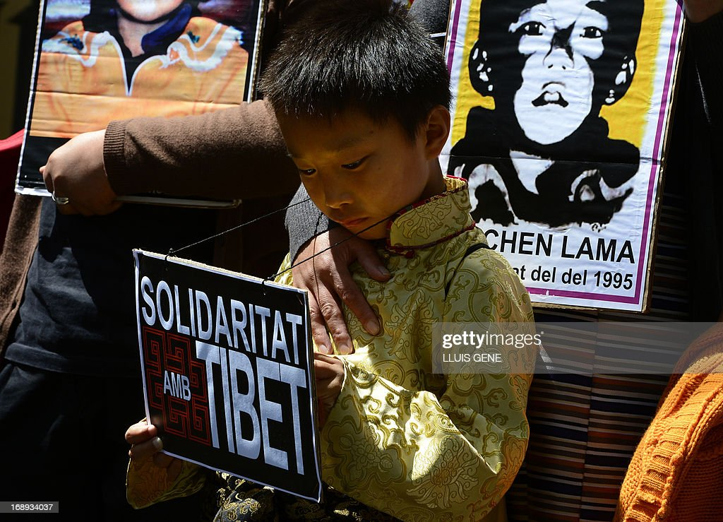 Pro-Tibetan protestors hold picures of Gendun Cheokyi Nyima (The Panchen Lama) during a demonstration outside the Chinese consulate in Barcelona on May 17, 2013 in Barcelona, to demand human rights freedom in Tibet and dialogue between the Dalai Lama and Beijing.