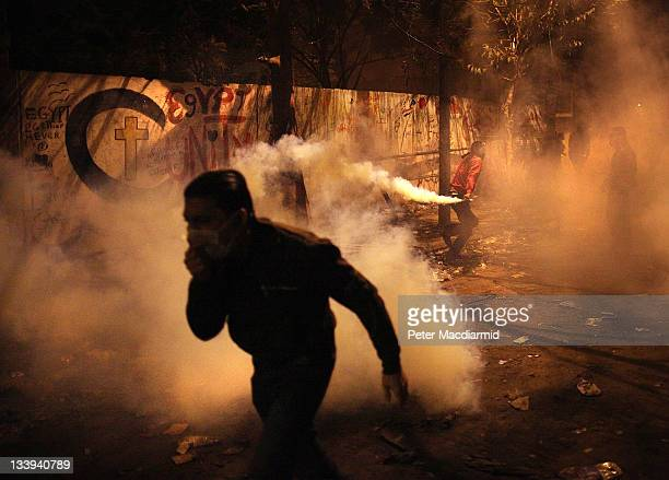 A prototestor runs as another throws a tear gas cannister back at police lines near Tahrir Square on November 22 2011 in Cairo Egypt Thousands of...