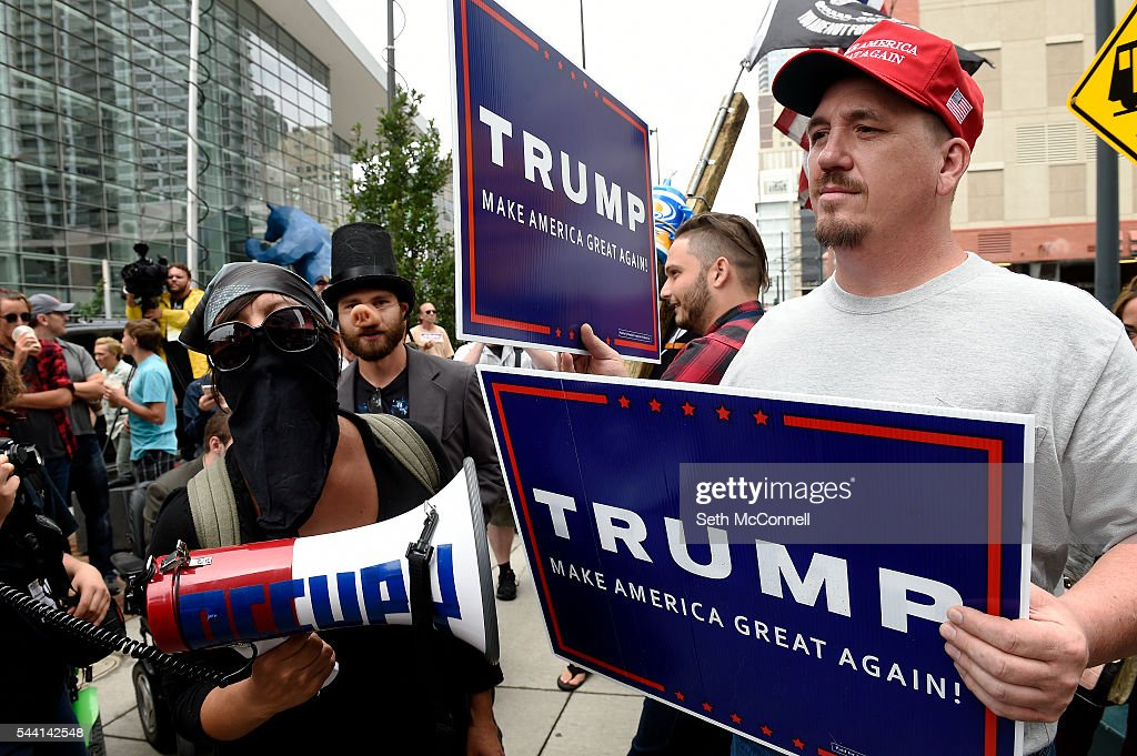 Pro-Trump supporter Greg, no last name given, uses a sign to block out a protestors megaphone during an Anti-Trump rally at the corner of 14th and California in Denver, Colorado on July 1, 2016.
