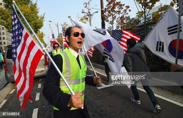 ProTrump supporters carry the US and South Korean flags during a rally welcoming US President Donald Trump's visit near the National Assembly in...