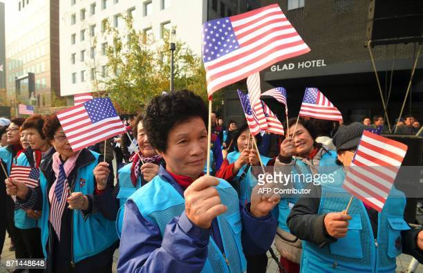 ProTrump supporters wave the US flags during a rally welcoming US President Donald Trump's visit near the National Assembly in Seoul on November 8...